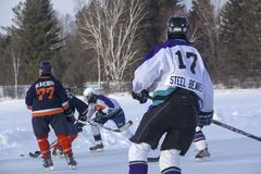 Women`s teams compete in a Pond Hockey Festival in Rangeley. Rangeley, Maine, USA - February 4, 2017: Women`s teams compete on the ice at the 11th annual New Royalty Free Stock Photo