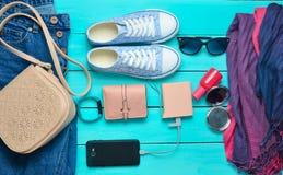 Women& x27; s in toebehoren, schoenen, kleren en moderne gadgets op een blauwe houten achtergrond royalty-vrije stock foto's