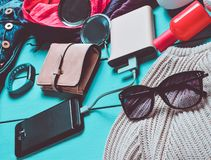 Women& x27; s in toebehoren, schoenen, kleren en moderne gadgets op een blauwe houten achtergrond Jeans, zak, tennisschoenen, sma stock foto