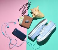 Women's travel accessories on a colored paper background. Sneakers, purse, passport, sunglasses, flash drive, smartphone. Headphones. Top view. Flat lay Stock Image