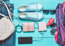 Women's trendy accessories, shoes, clothes and modern gadgets on a blue wooden background. Jeans, bag, sneakers, smartphone. Smart bracelet, power bank stock photo