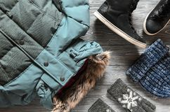 Women`s warm winter clothing and accessories - jacket, black lea. Ther high top sneakers, gloves and hat. Wish list or shopping overview concept. Fashion concept Royalty Free Stock Photography