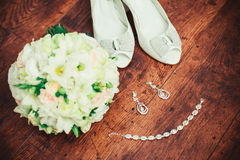 Women's wedding accessories. Wedding bouquet, white shoes and diamond jewelry on a wood background. Beautiful set of women's wedding accessories Stock Images