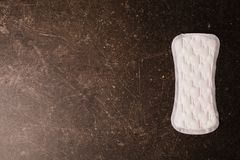 Women`s white daytime hygiene pads on a dark marble background Stock Photo