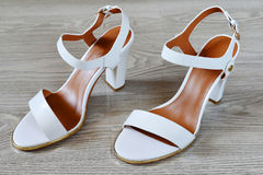 Women's white sandals  on  floor Royalty Free Stock Photos