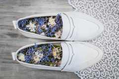 Women& x27;s white shoes with flowers inside and white lace. Women& x27;s white leather shoes with white and blue flowers inside and white lace on a light Stock Images