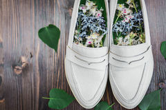 Women& x27;s white shoes with fresh flowers on the insole. Women& x27;s white shoes with white and blue flowers inside for flavoring and green leaves next to Royalty Free Stock Image
