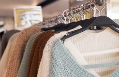 Women`s woolen knitted sweaters in a clothing store, close-up, front view royalty free stock photo
