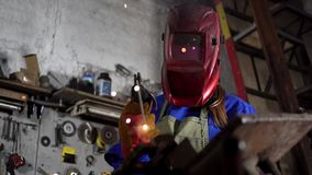 Cute welder girl in uniform in the garage working with welding equipment. Women`s work in art