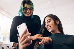 Women at salon looking at mobile phone Royalty Free Stock Photography