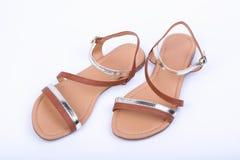 Women& x27; sandali di marrone di s su fondo bianco Vista superiore fotografia stock libera da diritti