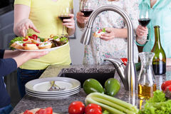 Women with sandwiches and glasses of wine standing in kitchen Stock Photos