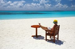 Women is on the sandy. A women sitting on the chair is reading royalty free stock photo