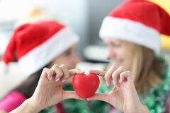 Women in santa claus hats hold red heart toy close-up