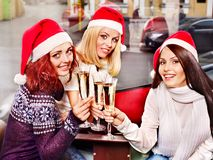 Women in santa hat drinking champagne. Women in santa hat drinking champagne in cafeteria Royalty Free Stock Image