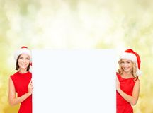 Women in santa helper hats with blank white board Royalty Free Stock Photography