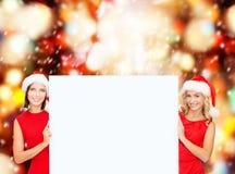 Women in santa helper hats with blank white board Royalty Free Stock Image