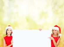 Women in santa helper hats with blank white board Stock Images
