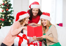 Women in santa helper hats with card and gifts Royalty Free Stock Photos