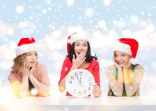 Women in santa helper hats with clock showing 12. Christmas, x-mas, winter, happiness concept - three smiling women in santa helper hats with clock showing 12 stock images