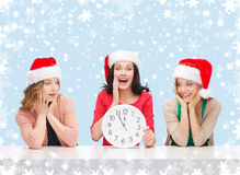Women in santa helper hats with clock showing 12. Christmas, x-mas, winter, happiness concept - three smiling women in santa helper hats with clock showing 12 royalty free stock photos