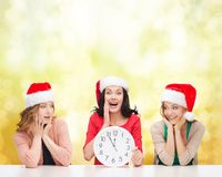 Women in santa helper hats with clock showing 12. Christmas, x-mas, winter, happiness concept - three smiling women in santa helper hats with clock showing 12 royalty free stock image