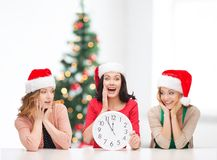Women in santa helper hats with clock showing 12. Christmas, x-mas, winter, happiness concept - three smiling women in santa helper hats with clock showing 12 stock photo