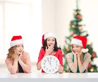 Women in santa helper hats with clock showing 12 Stock Photos