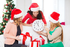 Women in santa helper hats with clock showing 12. Christmas, x-mas, winter, happiness concept - three smiling women in santa helper hats with clock showing 12 stock photos