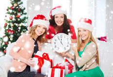 Women in santa helper hats with clock showing 12. Christmas, x-mas, winter, happiness concept - three smiling women in santa helper hats with clock showing 12 royalty free stock images
