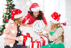 Women in santa helper hats with clock showing 12. Christmas, x-mas, winter, happiness concept - three smiling women in santa helper hats with clock showing 12 royalty free stock photography