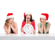 Women in santa helper hats with clock showing 12 Stock Photo