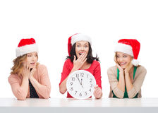 Women in santa helper hats with clock showing 12 Royalty Free Stock Image