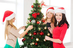 Women in santa helper hats decorating a tree Royalty Free Stock Images