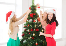 Women in santa helper hats decorating a tree Stock Photo