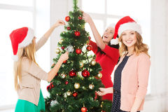 Women in santa helper hats decorating a tree Stock Photography