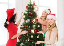 Women in santa helper hats decorating a tree Royalty Free Stock Photos