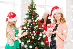 Women in santa helper hats decorating a tree Royalty Free Stock Photo
