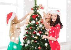 Women in santa helper hats decorating a tree Stock Photos