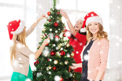 Women in santa helper hats decorating a tree Stock Image