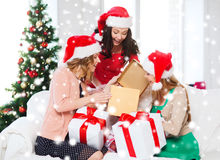 Women in santa helper hats with many gift boxes Stock Photo
