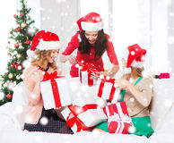 Women in santa helper hats with many gift boxes Stock Photos