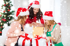 Women in santa helper hats with many gift boxes Royalty Free Stock Images