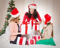 Women in santa helper hats with many gift boxes Royalty Free Stock Photography