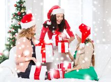 Women in santa helper hats with many gift boxes Stock Image