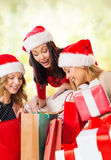 Women in santa helper hats with shopping bags Stock Image