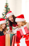 Women in santa helper hats with shopping bags Stock Photos