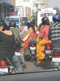 Women in sarees ride side saddle Stock Photo