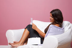 Women sat in an armchair reading a letter Royalty Free Stock Image