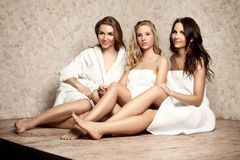 Women in a sauna. Three beautiful women in a white bathrobe and in a white towels sitting in a sauna. Boudoir photography Stock Photography
